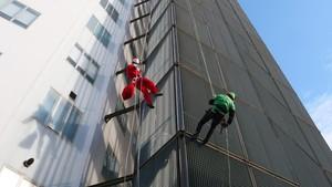 Papá Noel baja haciendo rápel por la fachada de Vall dHebron.