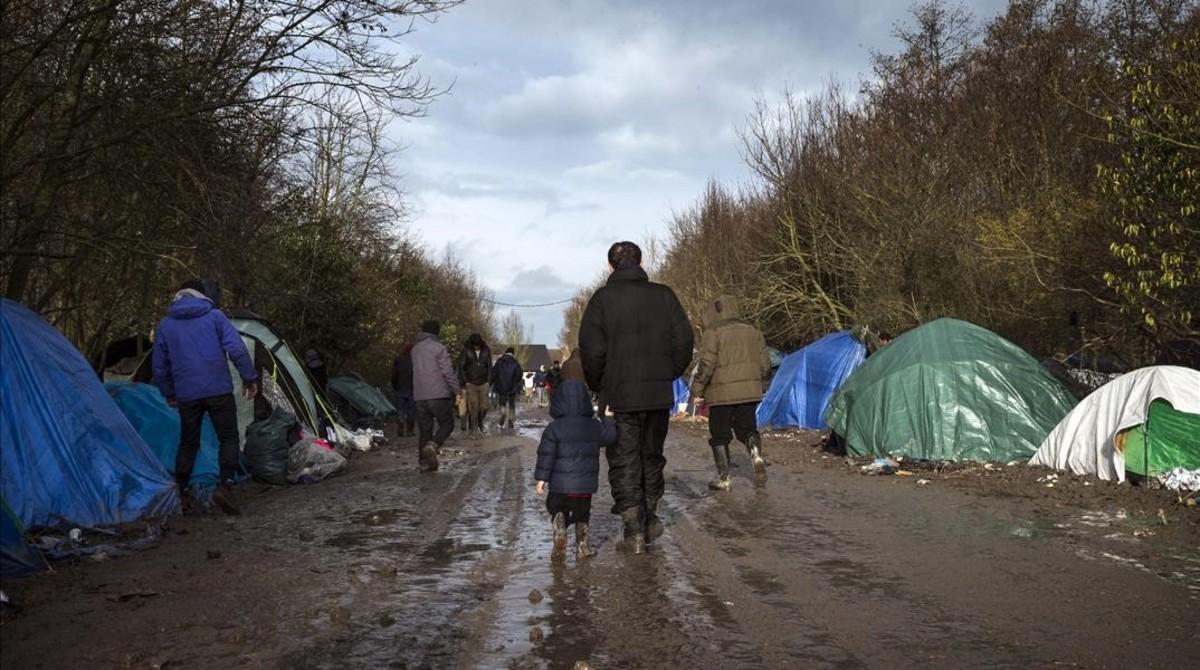 Un refugiado kurdo camina con su hijo por el campamento temporal montado en Grande-Synthe, cerca de Dunkerque, en el norte de Francia, el pasado 11 de enero.