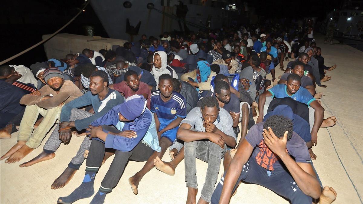 Un grupo de refugiados esperan en una base naval de Libia después de ser resctadaos en el Mediterráneo.