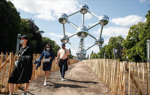 Unas personas con mascarillas pasean alrededor del Atomium de Bruselas, este lunes, coincidiendo con la reunión de la OMS que se coordina desde la capital europea.
