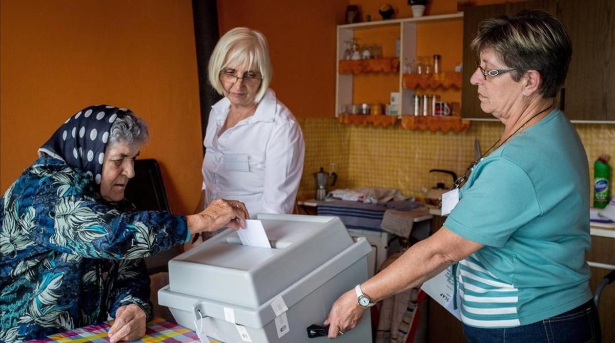 Una anciana introduce su papeleta en una urna sostenida por miembros de una mesa electoral, en Kelebia, a 191 kilómetros al sur de Budapest.