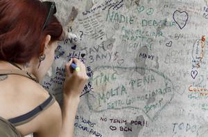 Una joven muestra sus condolencias con un mensaje escrito en un árbol de la Rambla de Barcelona.
