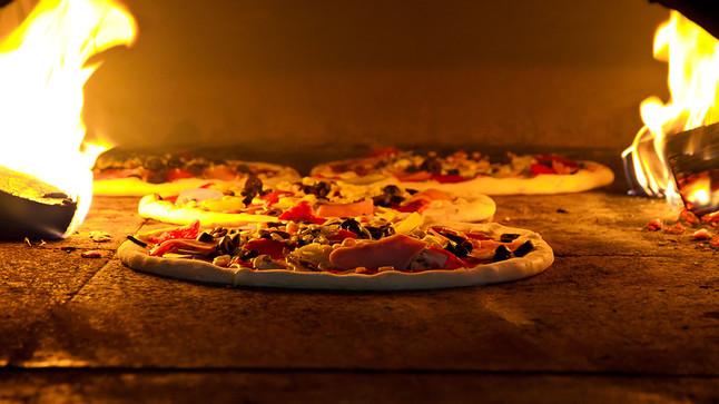 Una pizza preparándose en un horno de leña.