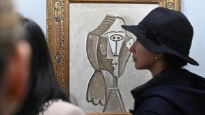 Varios visitantes conversan delante de la obraRetrato de Jaquelinede Pablo Ruiz Picasso.