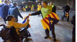 Un voluntari reparteix estelades a les portes del Camp Nou, abans del Barça-Bate.