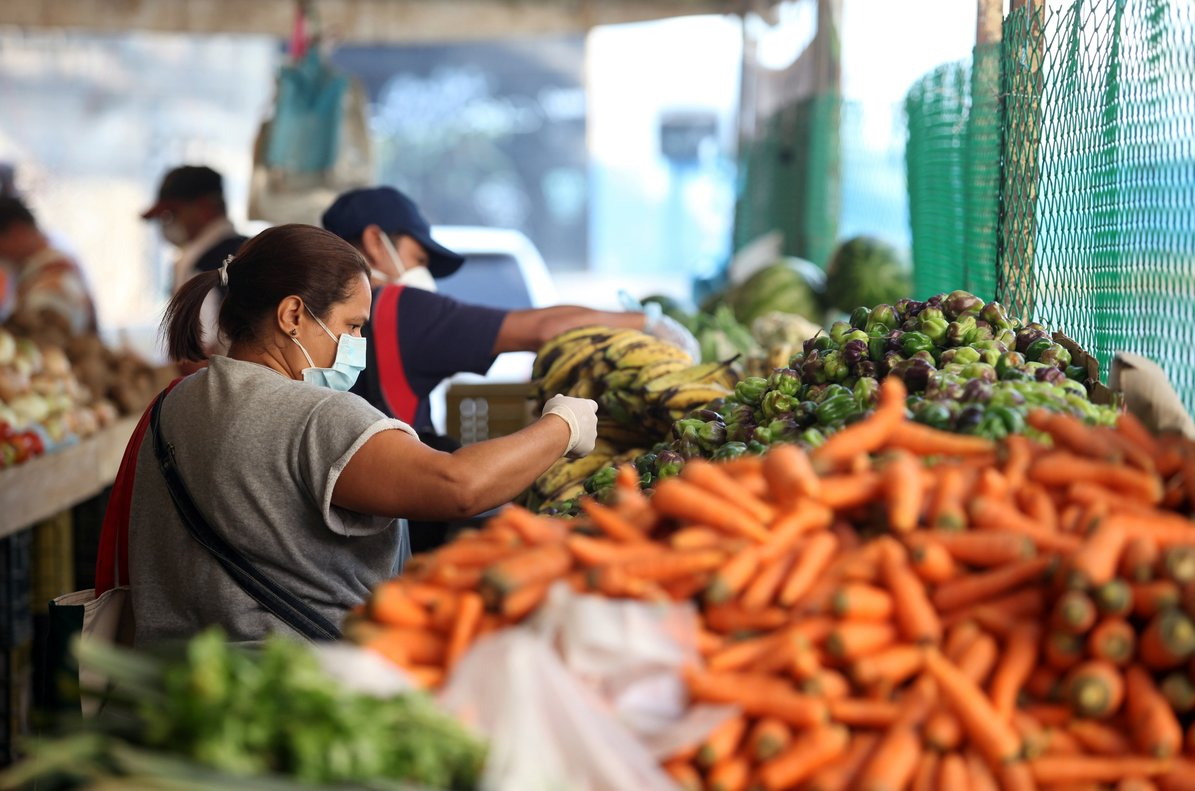 A woman wearing a protective mask picks vegetables in a street market during the nationwide quarantine in response to the spread of coronavirus disease (COVID-19) in Caracas, Venezuela March 31, 2020. REUTERS/Fausto Torrealba NO RESALES. NO ARCHIVE.