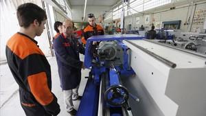 Un profesor explica el uso de una máquinaa sus alumnos en el instituto El Calamot, en Gavà (Baix Llobregat).