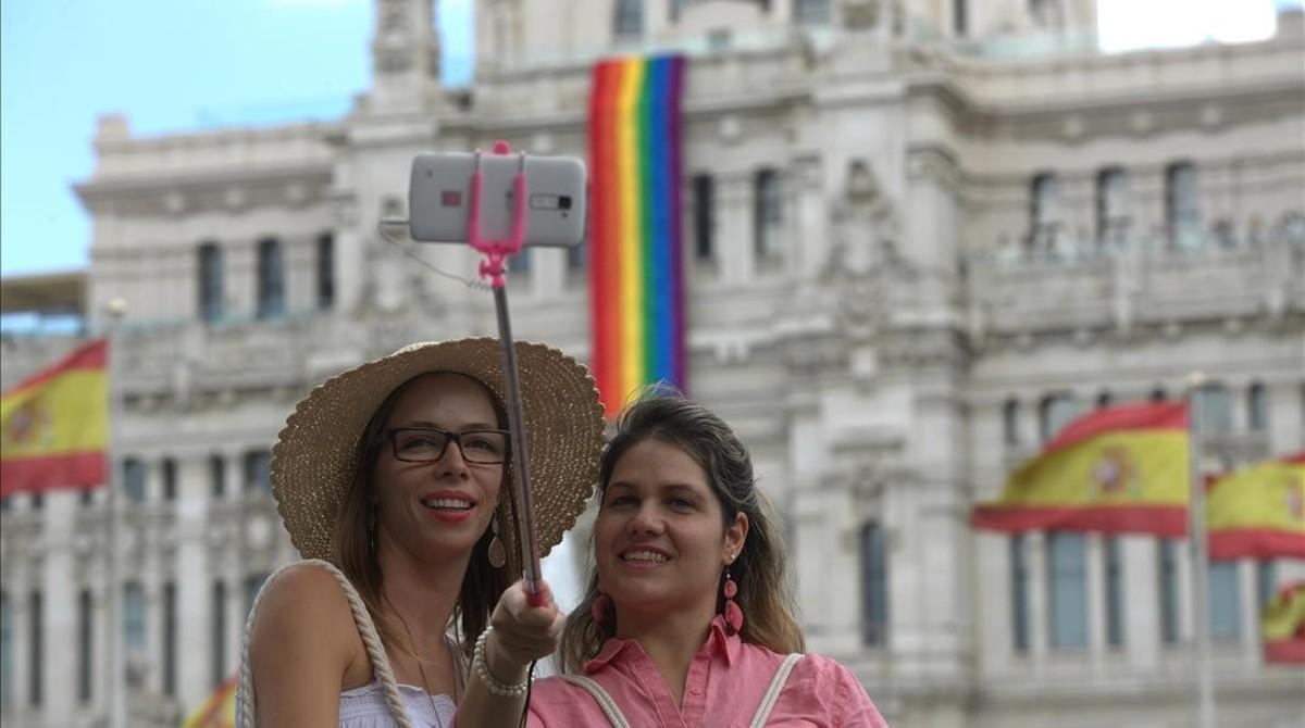 Dos turistas se hacen un selfie frente al Ayuntamiento de Madrid, que luce la bandera del arcoiris.