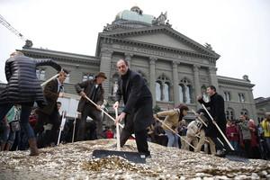 Activistas colocan céntimos en el suelo a las puertas del Parlamento en Berna, el pasado día 4.
