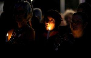 Residentes encienden velas durante una vigilia para mostrar su solidaridad y rendir homenaje a las victimas del ataque.