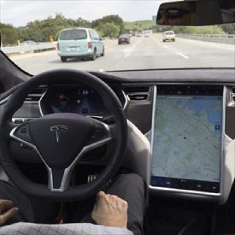 Un coche de Tesla con el piloto automático de conducción autónoma activado.
