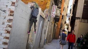 Uno de los menores del 'Forat de la Vergonya', saltando del solar en el que duereme, el lunes pasado. (Archivo).