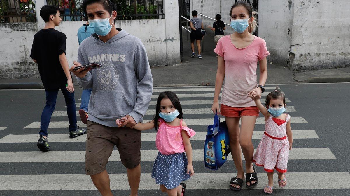 Una familia con mascarillas en Manila, Filipinas.