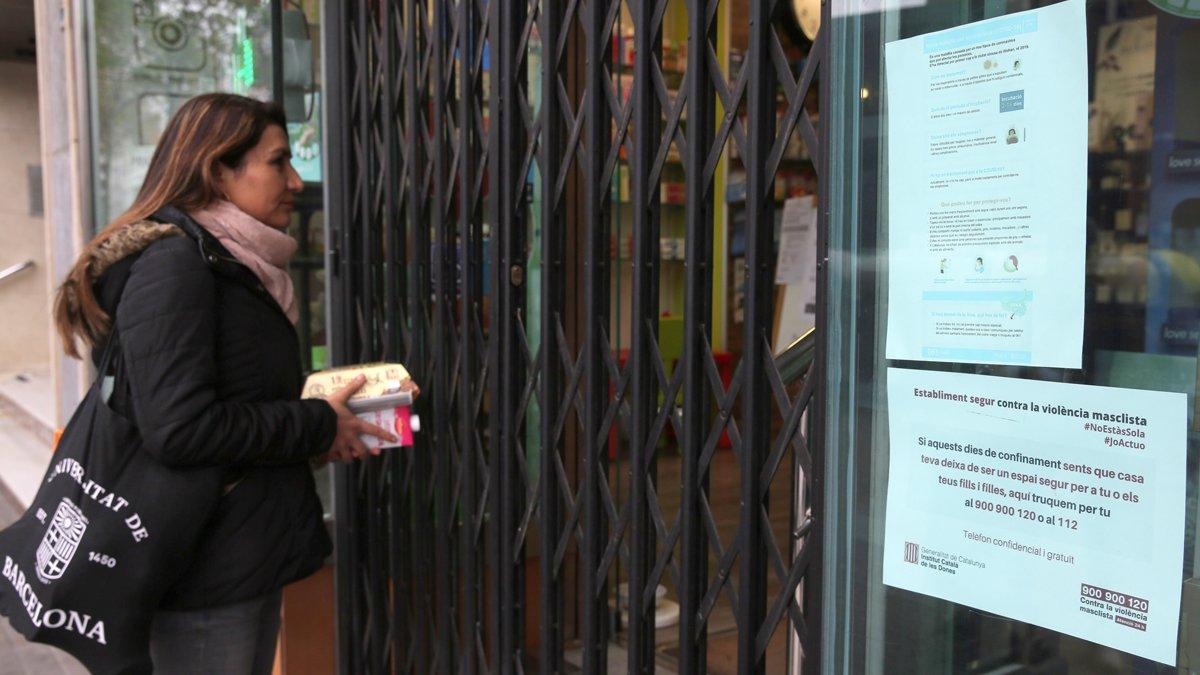 Una mujer ante un establecimiento donde se informa sobre recursos de apoyo a víctimas de violencia machista.