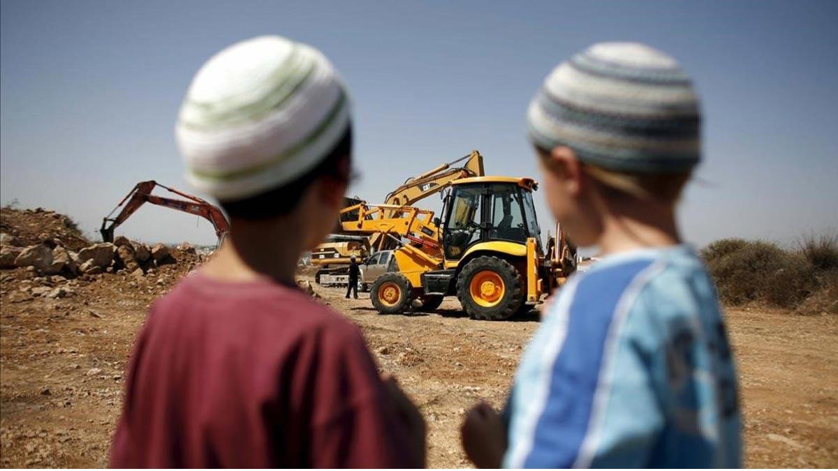 Estados Unidos deja de considerar ilegales los asentamientos israelís en Cisjordania. En la foto, dos niños judíos observan una retroexcavadora utilizada en la construcción de unas 50 viviendas en el asentamiento judío de Ariel.