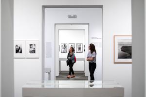 Dos visitantes contemplan las fotografías de esta exposición.