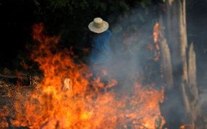 FILE PHOTO: A man works in a burning tract of Amazon jungle as it is being cleared by loggers and farmers in Iranduba, Amazonas state, Brazil August 20, 2019. REUTERS/Bruno Kelly/File Photo