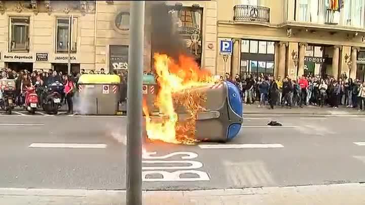 Un grupo encapuchado, destroza las lunas de un banco y queman un contenedor. en la manifestación de estudiantes en Barcelona.