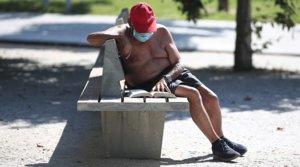 Un hombre con mascarilla lee un libro en un parque de Madrid, el pasado 23 de junio.