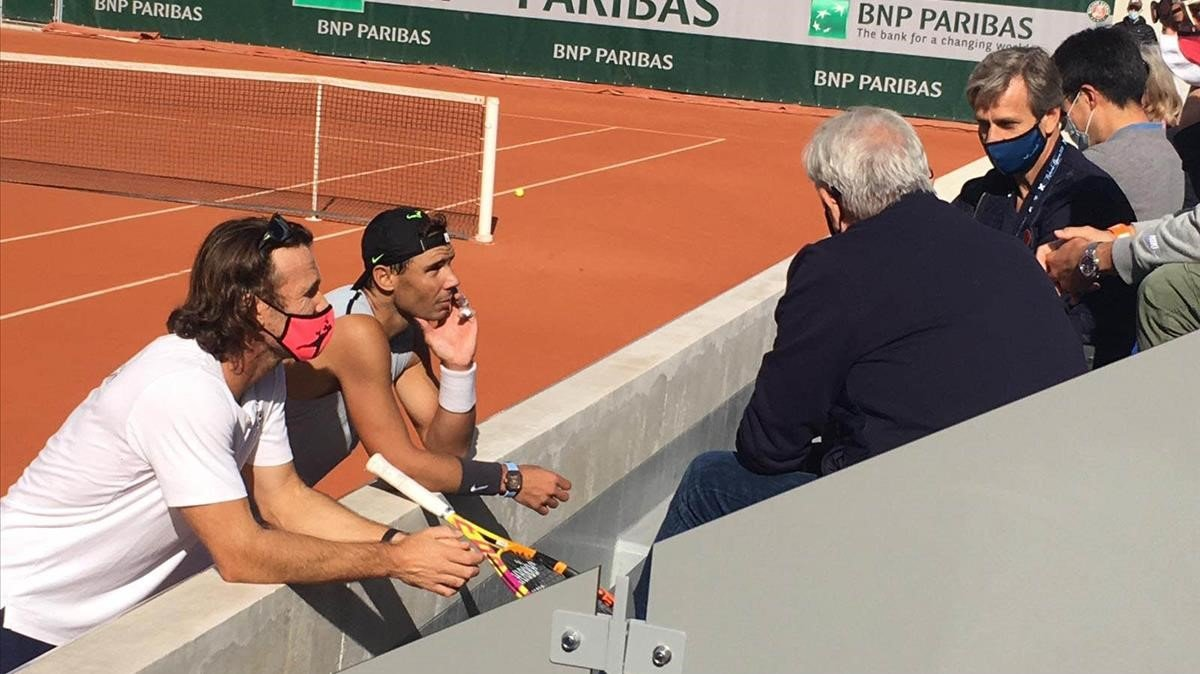 Nadal y Moyà conversan con su equipo, al final del entrenamiento en Roland Garros.