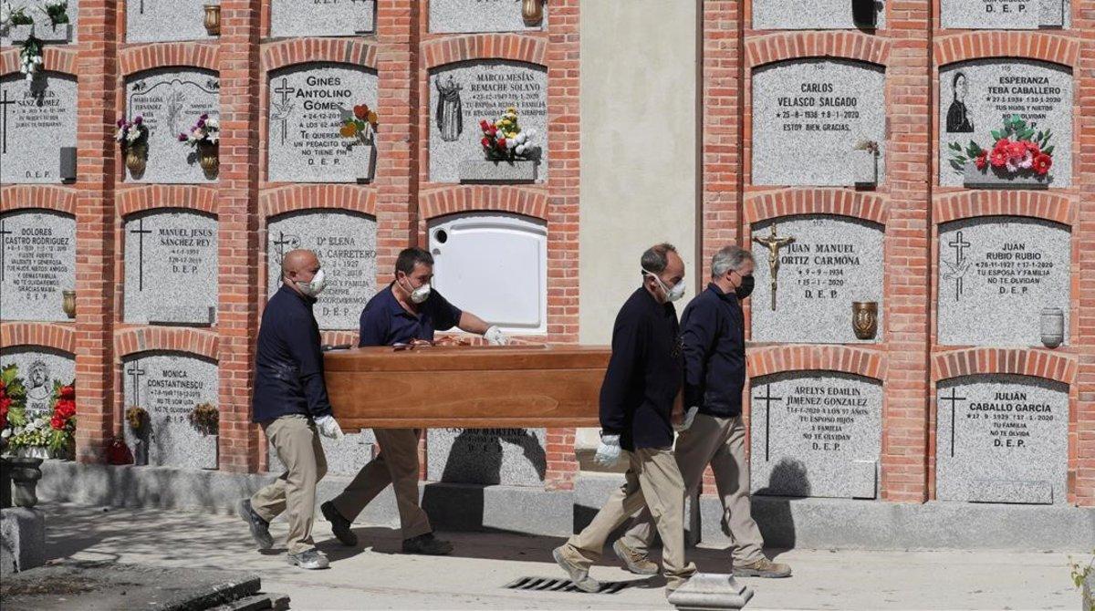Operarios trasladan un féretro en el cementerio de la Almudena, en Madrid.