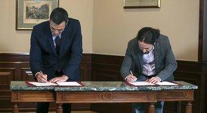 Pedro Sánchez y Pablo Iglesias firman el preacuerdo de coalición, el martes pasado en el Congreso.