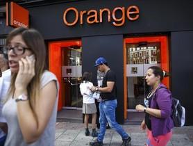 Personas pasan por delante de una tienda de Orange en Madrid.