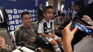 Cristiano Ronaldo se hace una foto junto a un niño con la camiseta dela Juventus en Yeda.