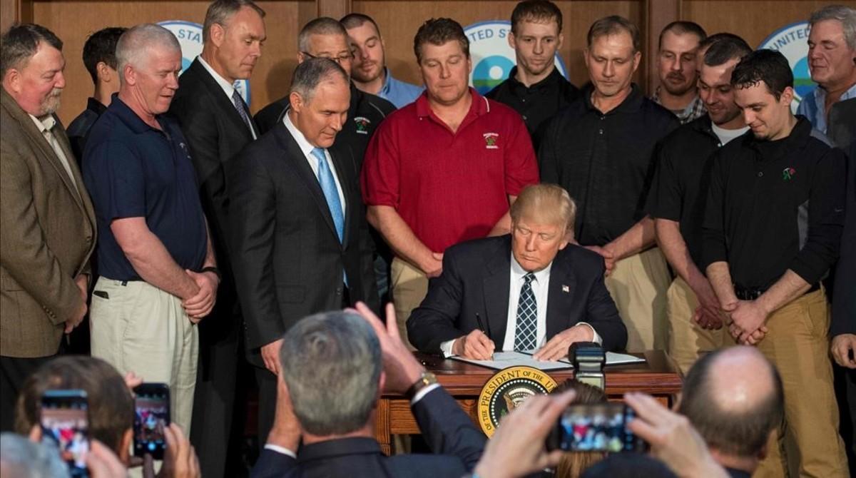 Trump, rodeado de mineros, firma la orden ejecutiva que pone los cimientos para deshacer la política medioambiental de Obama.