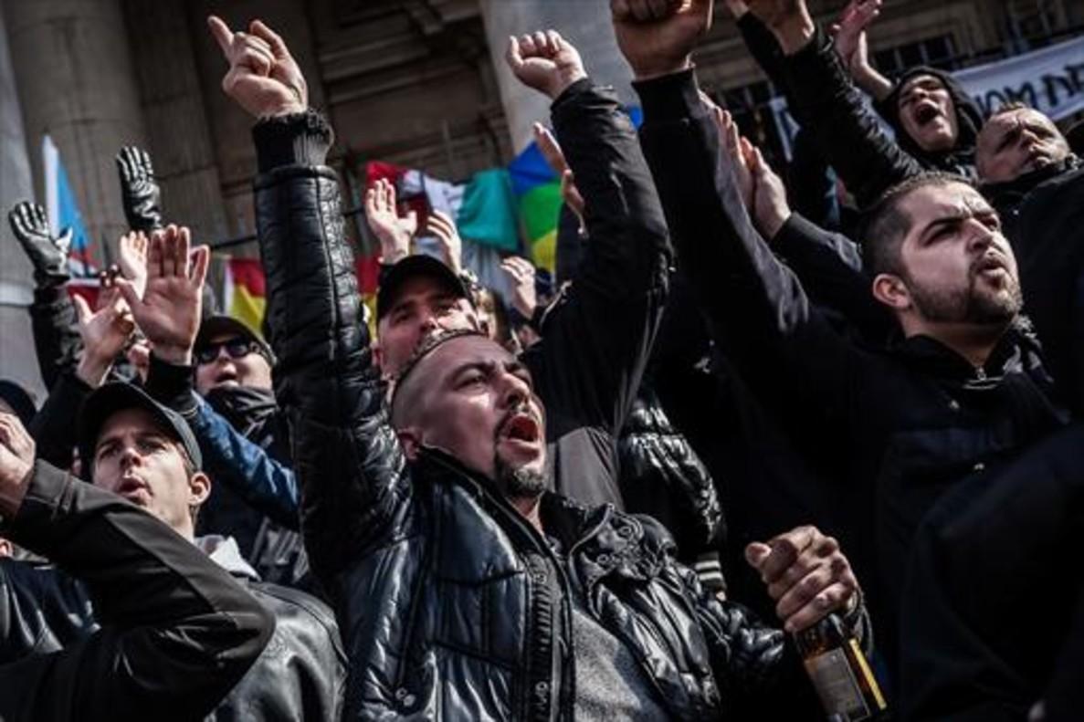 Un grupo de ultras lanzan consignas xenófobasen la plaza de la Bolsa de Bruselas.