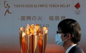 Un ciudadano japonés pasea junto a la antorcha olímpica.