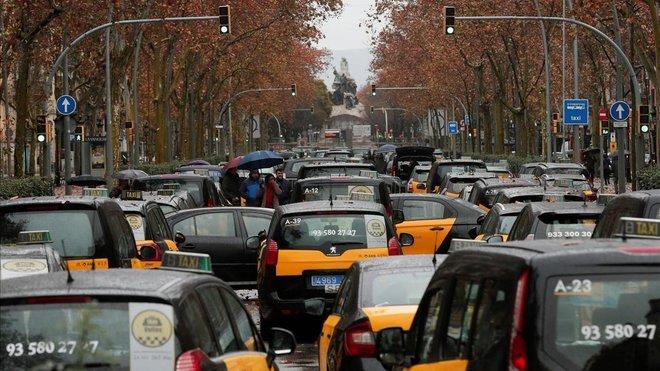 Decenas de taxis cortan la Gran Via de Barcelona.
