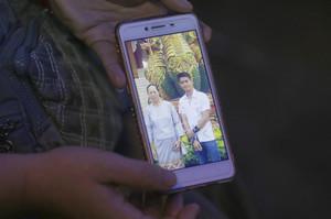 La tia del entrenador Ekapol Chantawong muestra una foto de móvil en la que aparece él y su abuela.
