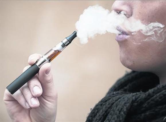 Una fumadora de cigarrillo electrónico exhala vapor tras una inhalación.