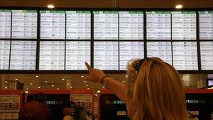 Imagen de archivo de una mujer señalando el panel de información de los trenes de Rodalies de Renfe en la estación de Sants.