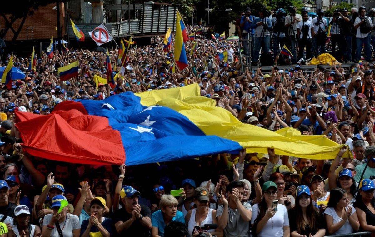 Venezolanos escuchan a Juan Guaido en las calles de Caracas.