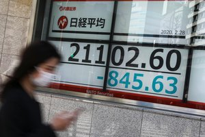 A woman wearing a protective face mask, following an outbreak of the coronavirus, walks past a screen showing Nikkei index, outside a brokerage in Tokyo, Japan February 28, 2020. REUTERS/Athit Perawongmetha
