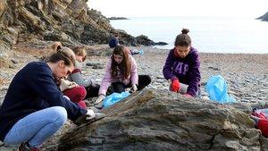 Un grupo de voluntarios limpia los restos de crudo de unas rocas en una cala del Cap de Creus, este domingo.