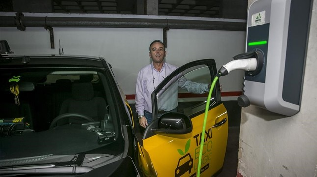 El taxista Paco Guerrero, junto al punto de recarga instalado en su plaza de aparcamiento en Barcelona.