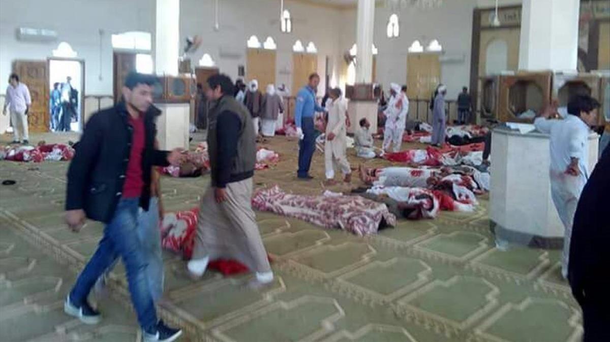 Varias personas permanecen junto a cuerpos sin vida en el interior de la mezquita atacada, en Al Arish, en el norte del Sinaí, el 24 de noviembre.