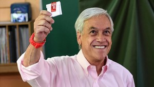Piñera sonríe mostrando su papeleta, antes de votar, en Santiago de Chile, el 17 de diciembre.