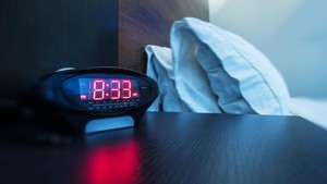 Un reloj-despertador en una mesilla de noche, junto a una cama.