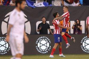 Los jugadores del Atlético Trippier (d) y Costa celebran uno de los goles ante el Madrid.