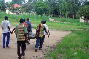Residentes en una aldea del Congo trasladan el cadáver de una víctima de los choques del Ejército con el ADF.