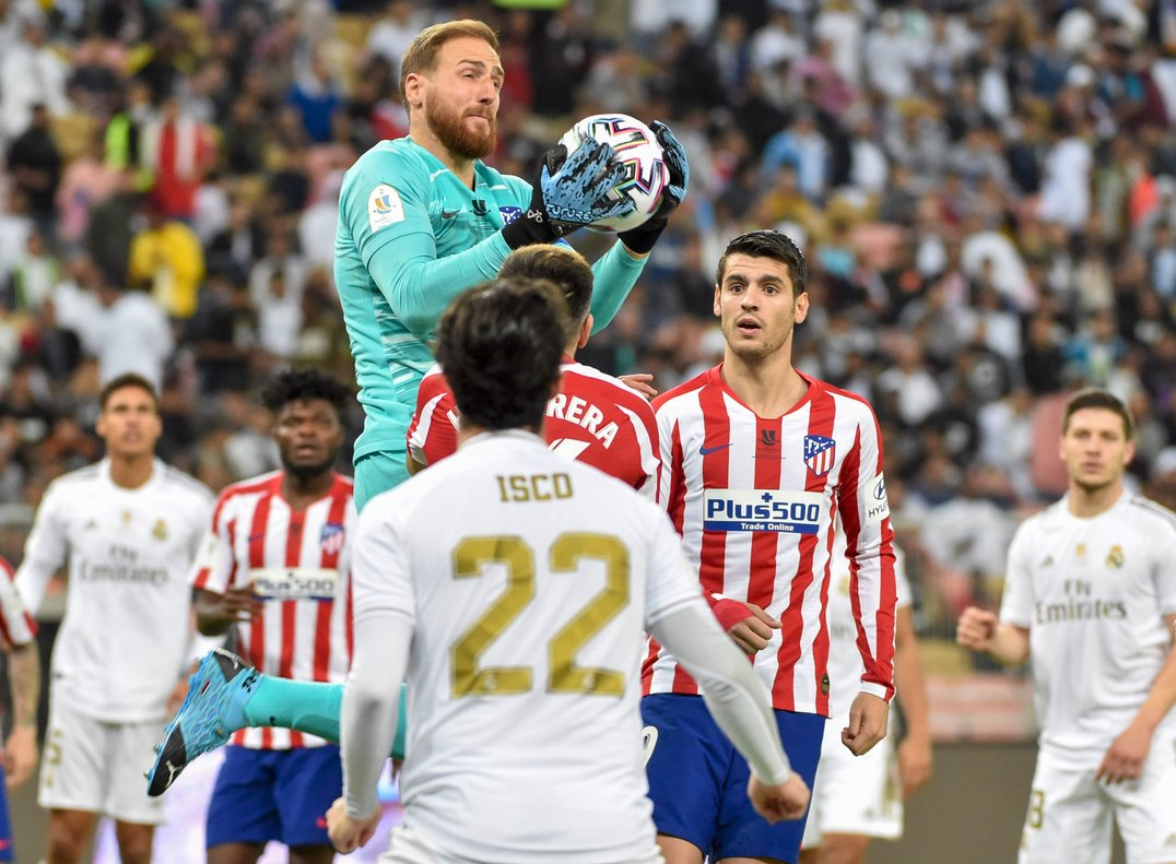 El portero del Atlético Jan Oblak detiene un balón durante el partido ante el Madrid.