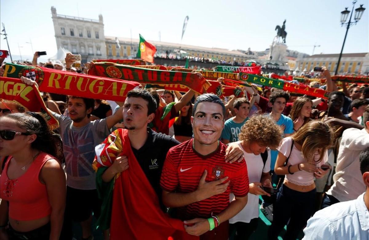 Aficionados portuguesesl cantanel himno portugués antes de ver el partido de la Eurocopa 2016 entre Portugal y Hungríaen el centro de Lisboa.