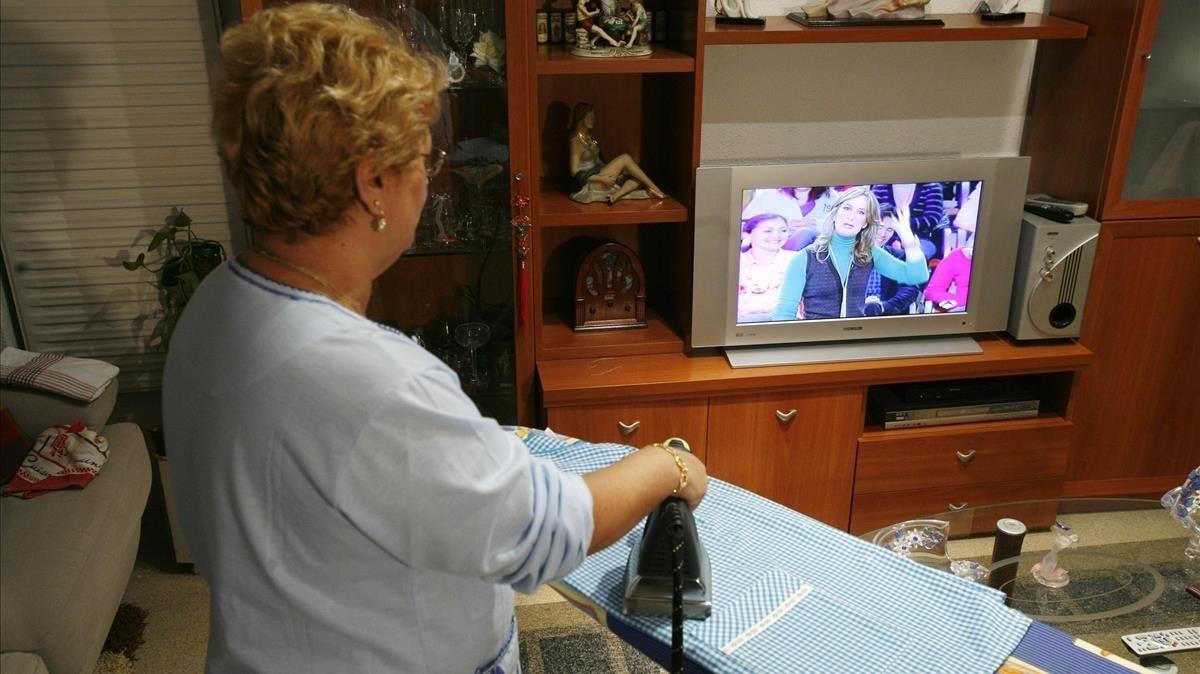 Ama de casa sigue un programa de televisión, mientras realiza labores del hogar.
