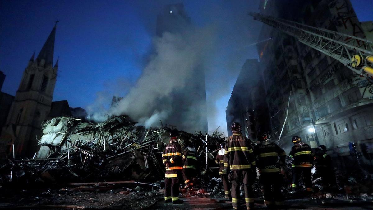 Bomberos junto al edificio que ha colapsado tras un incendio.