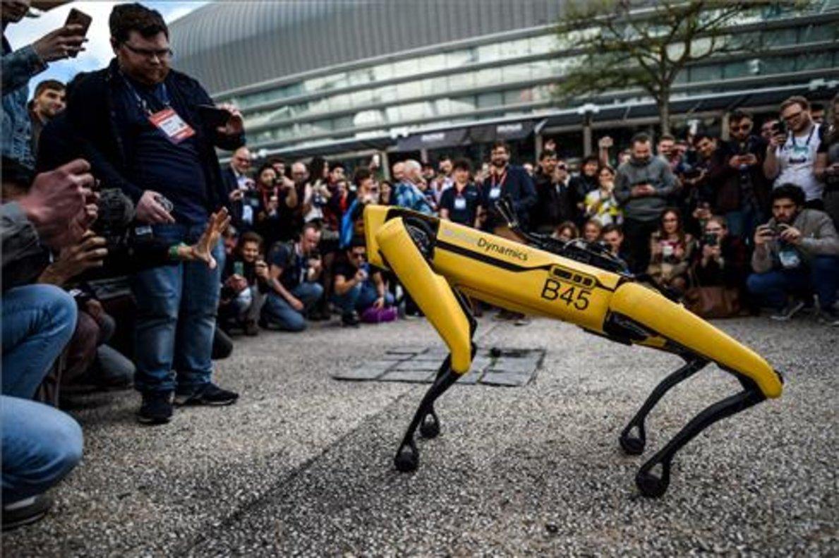 Varios asistentes al Web Summit de Lisboa fotografían a Spot, el perro robot de Boston Dynamics.