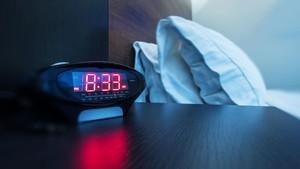 CAMBIO DE HORA. Un reloj-despertador, en una mesilla de noche.